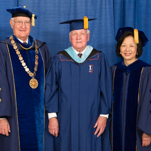 Dale Flach, dressed in cap and gown, flanked by University of Illinois President Robert Easter and Chancellor Phyllis Wise.